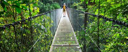 Walking across a hanging chain and link fence in Costa Rica exploring the wildlife from the canopy